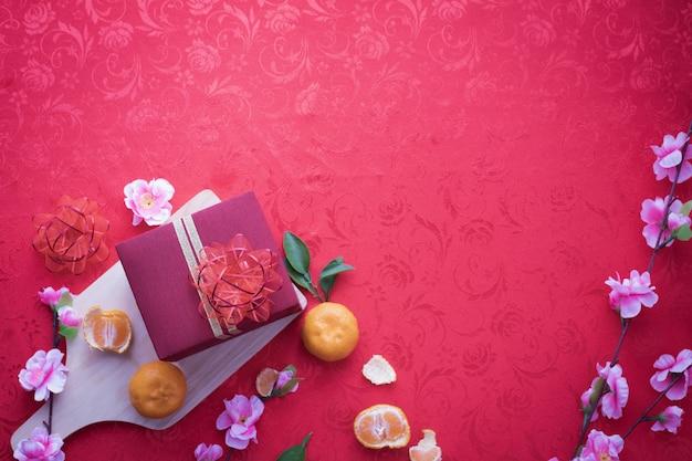 Contenitore di regalo e fiore di ciliegia con lo spazio della copia per testo sul fondo rosso di struttura.