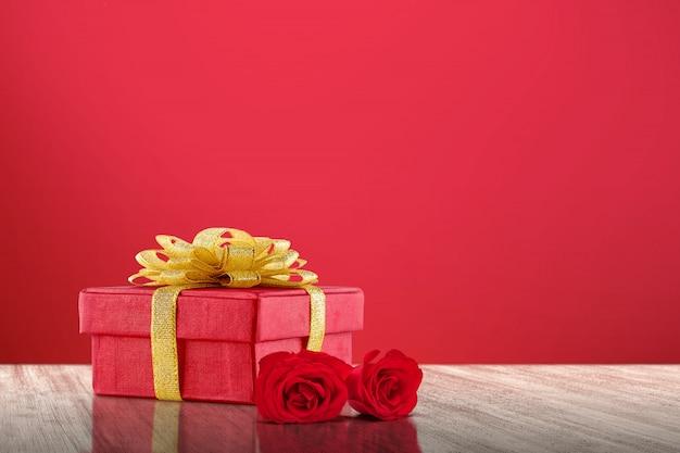 Contenitore di regalo e rose rosse su un fondo di legno del pavimento