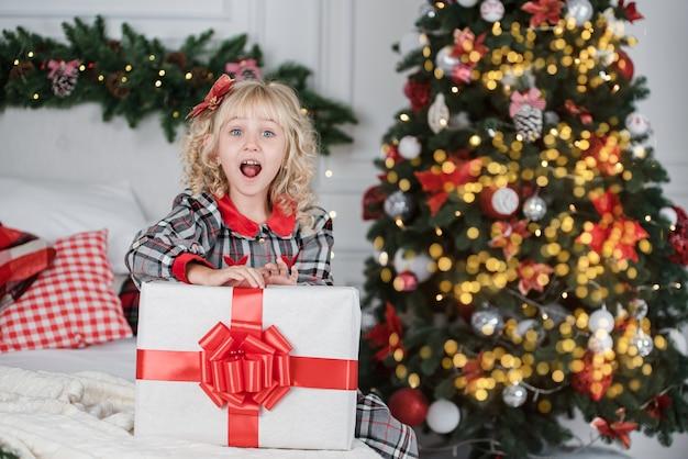 Contenitore di regalo emozionante felice di natale della tenuta del bambino della ragazza.