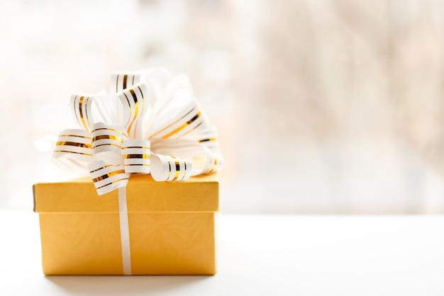Contenitore di regalo giallo avvolto in nastro a strisce bianco e oro su sfondo chiaro.