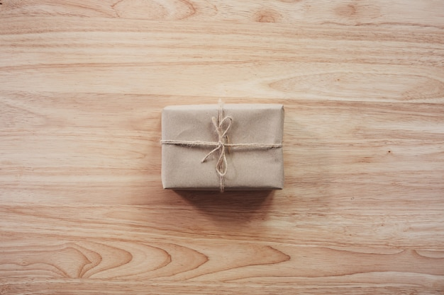 Contenitore di regalo marrone sulla tavola di legno