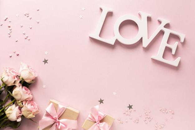 Contenitore di regalo o contenitore e fiori di regalo sulla vista rosa del piano d'appoggio.