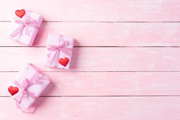 Contenitore di regalo rosa con cuore rosso e fiori su fondo di legno rosa.
