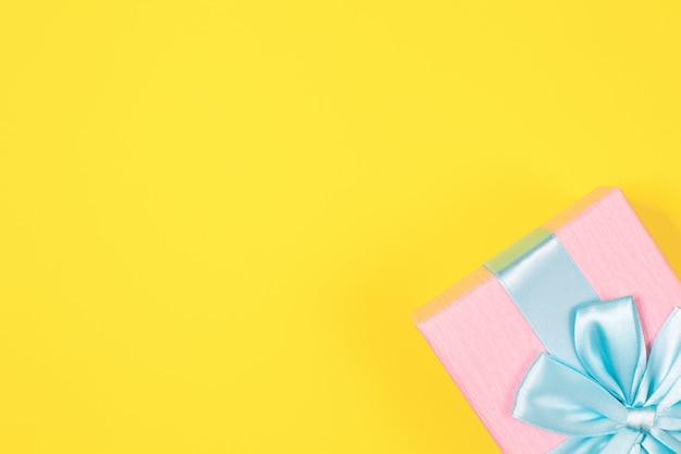 Contenitore di regalo rosa legato con il nastro blu con l'arco in alto a sfondo giallo. copia spazio