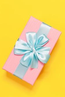 Contenitore di regalo rosa legato con il nastro blu con l'arco in alto a sfondo giallo.