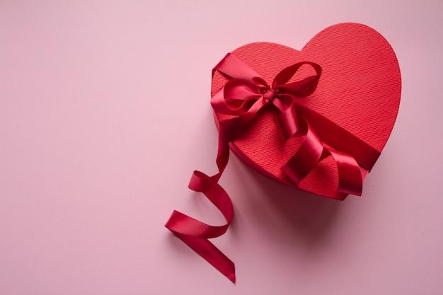 Contenitore di regalo rosso a forma di cuore con nastro rosso