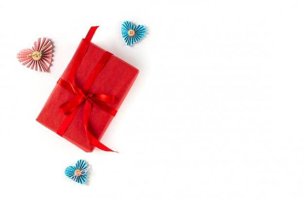 Contenitore di regalo rosso con cuore e l'arco su fondo bianco. san valentino 14 febbraio concetto di confezionamento. vista piana, copia spazio, vista dall'alto.