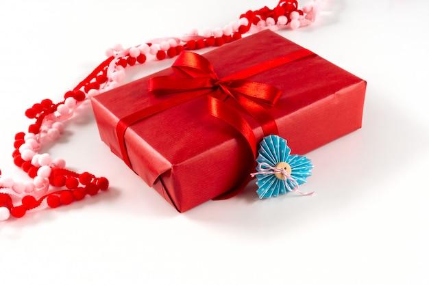 Contenitore di regalo rosso con cuore e l'arco su fondo bianco. san valentino 14 febbraio concetto di confezionamento.