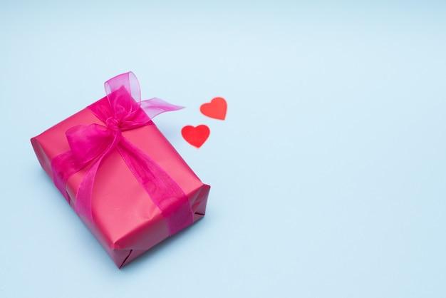 Contenitore di regalo rosso con cuore su fondo blu
