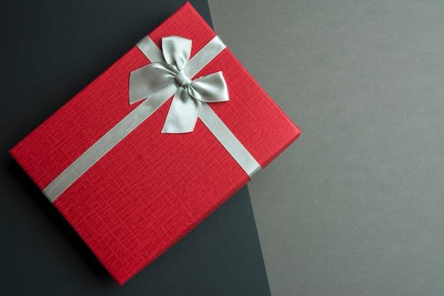 Contenitore di regalo rosso con fiocco su sfondo nero e grigio