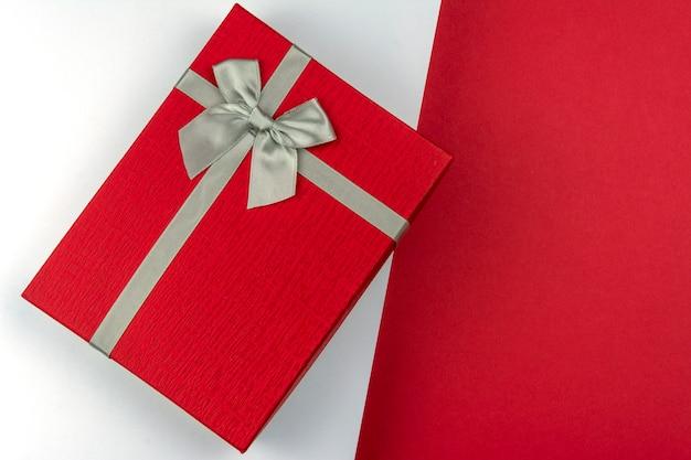 Contenitore di regalo rosso con l'arco su fondo rosso e bianco