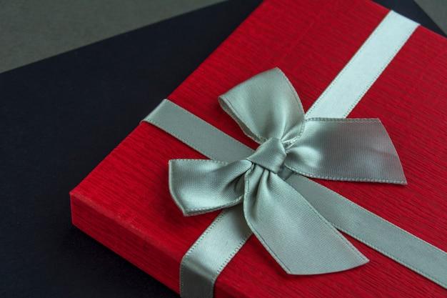 Contenitore di regalo rosso con sfondo nero e grigio di prua. avvicinamento