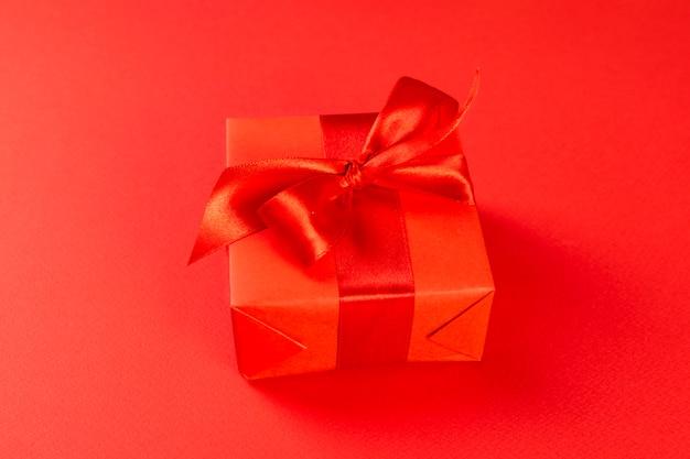 Contenitore di regalo rosso con un nastro rosso su una priorità bassa rossa
