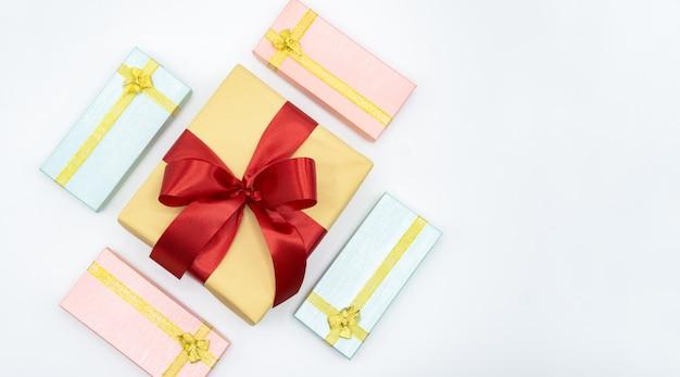 Contenitore di regalo rosso del nastro con la vista superiore del contenitore di regalo rosa e blu su bianco