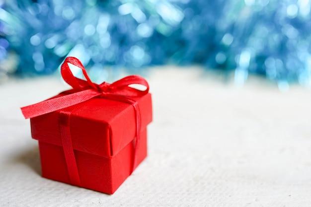 Contenitore di regalo rosso del nuovo anno su bianco con bokeh blu, spazio della copia. natale