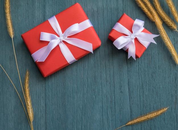 Contenitore di regalo rosso e fiore di erba secca su fondo di legno verde