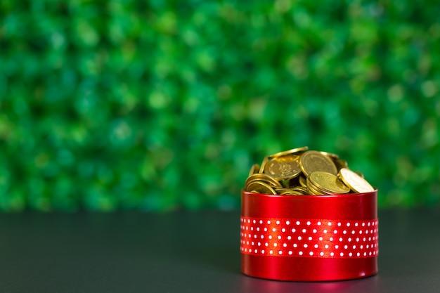 Contenitore di regalo rosso rotondo con fiocco di nastro sul tavolo nero e sfondo verde