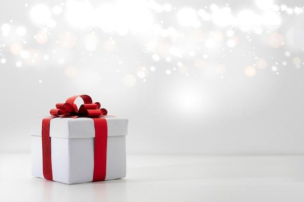 Contenitore di regalo rosso su fondo bianco, bokeh delle luci di natale