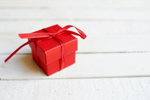 Contenitore di regalo rosso su fondo di legno bianco con lo spazio della copia