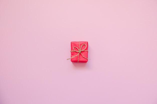 Contenitore di regalo rosso su sfondo rosa.
