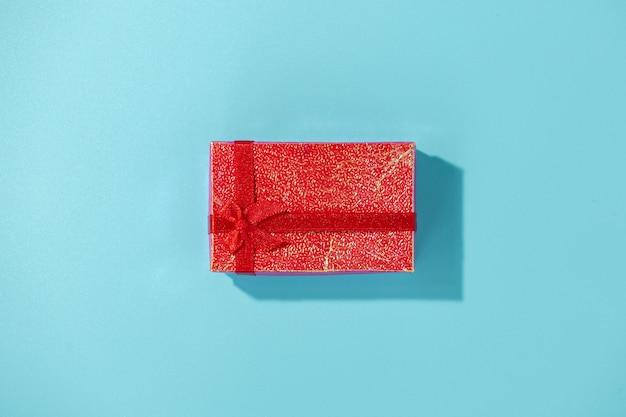 Contenitore di regalo rosso su superficie blu