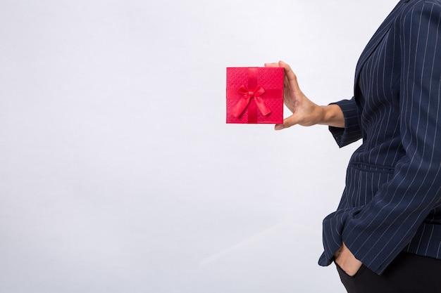Contenitore di regalo rosso tenuto da businesswomna