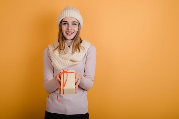 Contenitore di regalo sorridente grazioso della tenuta della ragazza ed esaminare macchina fotografica sopra fondo arancio