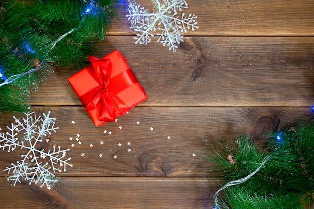 Contenitore di regalo su una tavola di legno, tavola con i rami del pino e palle rosse, concetto del nuovo anno