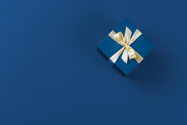 Contenitore di regalo sulla vista superiore del fondo blu classico