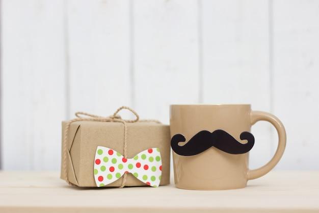 Contenitore di regalo, tazza di caffè, baffi di carta, legame su fondo di legno con lo spazio della copia. buona festa del papà.