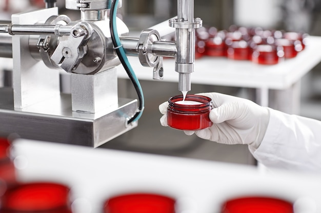 Contenitore di riempimento del lavoratore con crema nella fabbrica di cosmetici