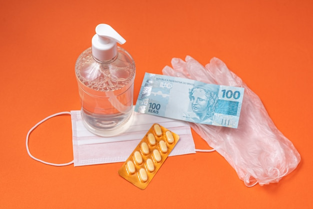 Contenitore in gel alcolico, maschera chirurgica, medicina e denaro reale brasiliano, sulla parete arancione
