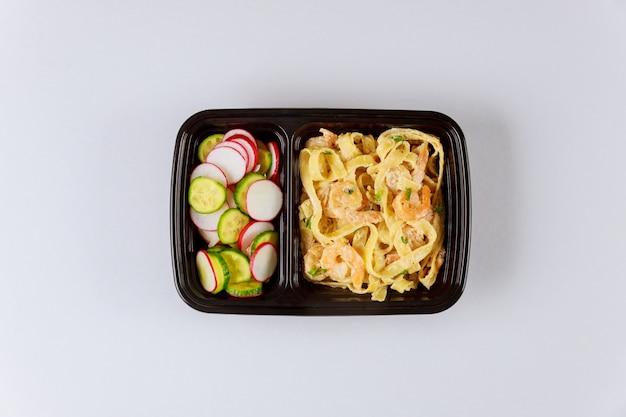 Contenitore in plastica nera con pasta, shrip e insalata fresca