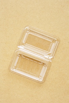 Contenitore per alimenti in plastica su sfondo di compensato.
