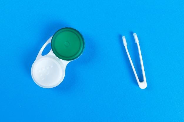 Contenitore per lenti a contatto e pinzette su sfondo blu