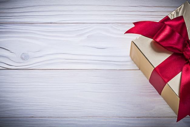 Contenitore-regalo con fiocco legato su tavola di legno