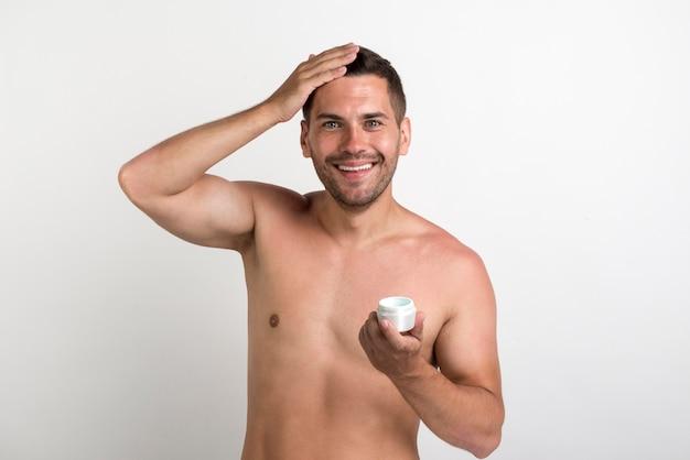 Contenitore sorridente della crema per capelli della tenuta del giovane ed esaminare macchina fotografica