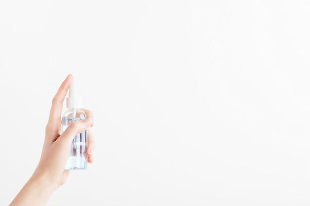 Contenitore trasparente per prodotti sterilizzatori con distributore. mano femminile che spinge sulla bottiglia di plastica senza marchio con il disinfettante.