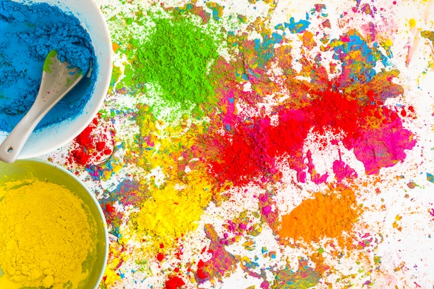 Contenitori con colori blu e gialli vicino al mucchio di colori secchi e luminosi