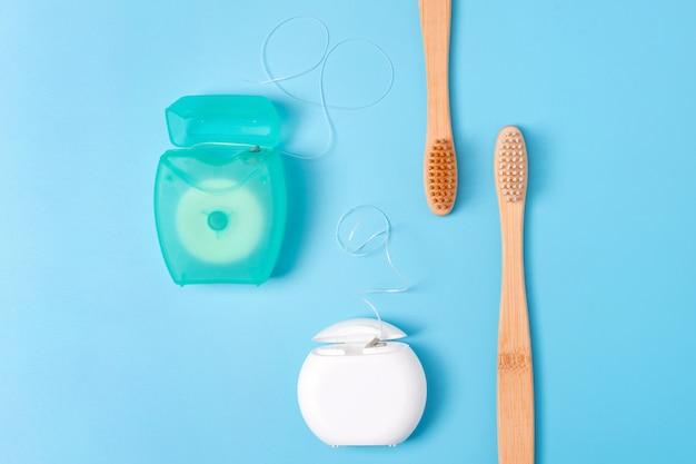 Contenitori del filo per i denti e spazzolini da denti di bambù su fondo blu. igiene orale quotidiana, cura dei denti e salute