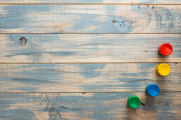 Contenitori dell'acquerello disposti su vecchia superficie di legno