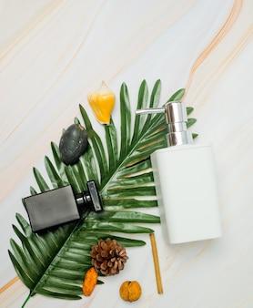 Contenitori di bottiglia di cosmetici naturali su foglia verde, bottiglia vuota, prodotto di bellezza naturale per la cura della pelle, concetto di prodotto di bellezza