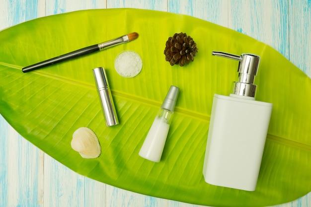 Contenitori di bottiglia di cosmetici naturali su foglia verde, bottiglia vuota