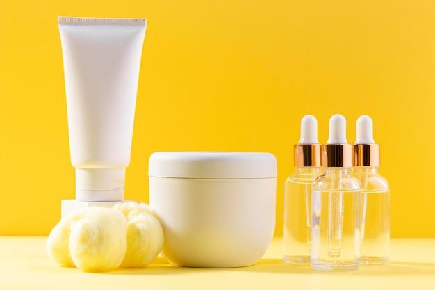 Contenitori di crema su sfondo giallo