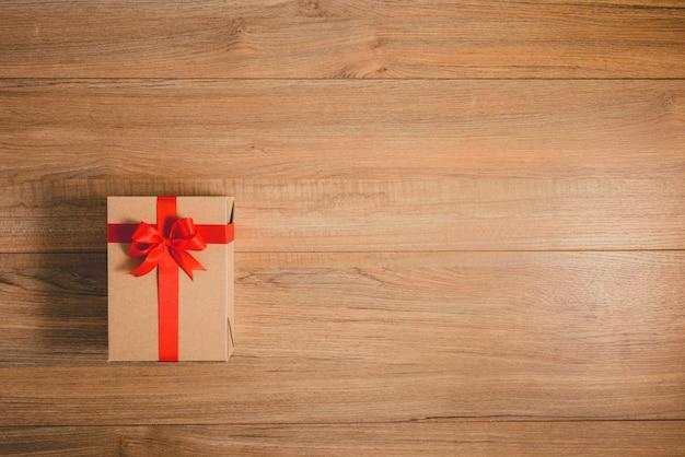 Contenitori di regali con i nastri festivi su fondo di legno