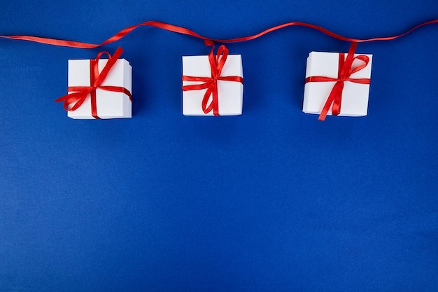 Contenitori di regalo bianchi di lusso con il nastro rosso sul fondo blu di colore di tendenza. san valentino, natale, regali per feste di compleanno. disteso. vista dall'alto.