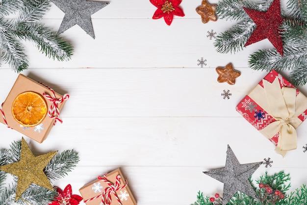 Contenitori di regalo con i rami dell'abete rosso della neve e la decorazione dei giocattoli su un fondo di legno bianco. biglietto natalizio. copriletto piatto