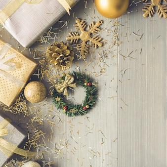 Contenitori di regalo d'argento e oro e articoli di decorazione di natale su fondo di legno