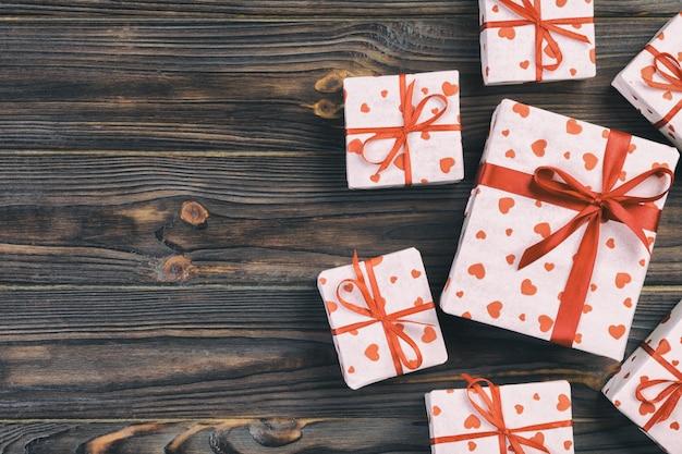Contenitori di regalo del biglietto di s. valentino su fondo di legno, copyspace