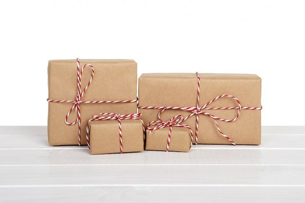 Contenitori di regalo di brown sulla tavola di legno grigia. isolato